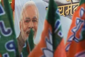 Bharatiya Janata Party (BJP) workers carry flags past a poster of Prime Minister Narendra Modi during an event to celebrate the reservation bill passed in Parliament, Mumbai, January 10.