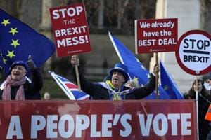 Anti-Brexit protesters hold signs outside the Houses of Parliament in London, Britain (File Photo)