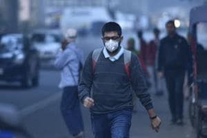 A man walks while wearing an aniti-pollution mask during a cold winter morning, at Karol Bagh in New Delhi on November 29, 2018.