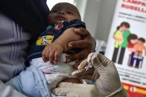 A medical worker injects a baby with a measles-rubella (MR) vaccine at a health centre.