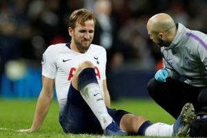 Harry Kane reacts as he receives treatment from the physio after sustaining an injury against Manchester United.