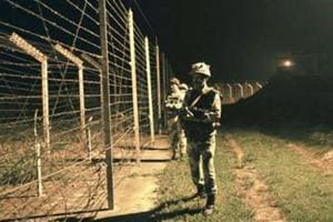 Border Security Force (BSF) soldiers standing guard during a night patrol near the fence at the India-Pakistan International Border at the outpost of Akhnoor sector, about 40 km from Jammu, on Sunday, October 2, 2016.