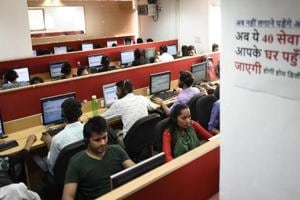 Customer care executives at a centre  receiving calls from people who wish to avail of doorstep delivery scheme.