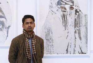Artist Jyotiprakash Sethy poses next to his artworks