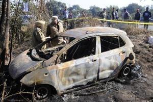 Police inspect a burned car near Sambalki village, Sector 82 in Mohali on Friday.