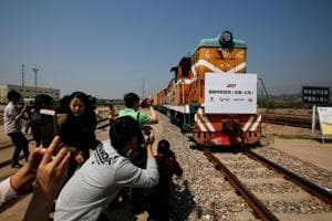 People take pictures as a train carrying containers from London arrives at the freight railway station in Yiwu, Zhejiang province, China, April 29, 2017.