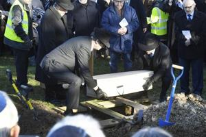 A coffin with the remains of six unidentified Holocaust victims is buried at the United Synagogue