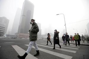 A man wearing a respiratory protection mask walks toward an office building during the smog after a red alert was issued for heavy air pollution in Beijing
