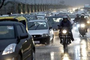 New Delhi: Traffic move on a street during rains as dark clouds hover over New Delhi, Tuesday morning, Jan 22, 2019.