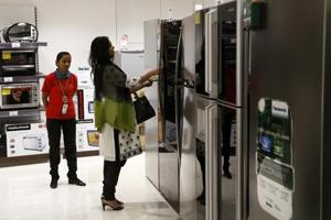 A customer inspects a refrigerator on display at a store in Mumbai.