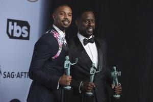Michael B Jordan, left, and Sterling K. Brown, winners of the award for outstanding performance by a cast in a motion picture for Black Panther pose in the press room at the 25th annual Screen Actors Guild Awards at the Shrine Auditorium.