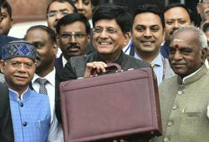 Finance Minister Piyush Goyal (C) displays a briefcase containing the Union budget to be presented at the Parliament today, outside his North Block office in New Delhi, Friday, 1 Feb, 2019.
