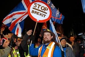 A pro-Brexit activist (L) remonstrates with an anti-Brexit activist (C) as both sides demonstrate outside of the Houses of Parliament in London.