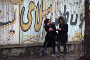 Afghan girls walk next to graffitis on a wall in Kabul on January 30.