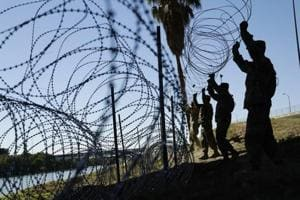 Members of the US military install multiple tiers of concertina wire along the banks of the Rio Grande near the Juarez-Lincoln Bridge at the U.S.-Mexico border, in Laredo, Texas on November 16.