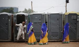 A groom comes out from a toilet as brides stand at the venue for a mass wedding ceremony, Ramlila Ground, New Delhi
