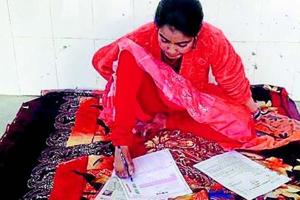 Ankita writes her intermediate exam papers using toes at Chapra Zila High School in Saran district.