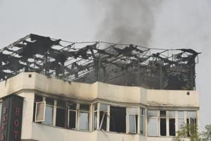 A black column of smoke rises after a massive fire broke out at Hotel Arpit Palace, Karol Bagh in New Delhi on February 12.