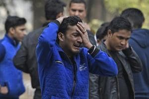A man breaks down after getting the news of his brother