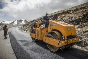 A Border Roads Organisation (BRO) worker drives a steamroller while repairing a road surface with tarmac on a section of the Leh Manali highway in Ladakh region.