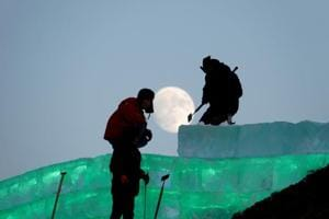 The moon shines as workers prepare an ice sculpture ahead of the Harbin International Ice and Snow Sculpture Festival in China.