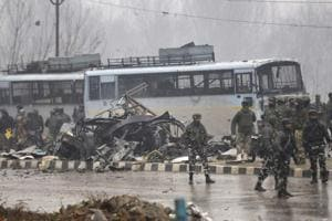 Security forces near the damaged vehicles at Lethpora on the Jammu-Srinagar highway, February 14