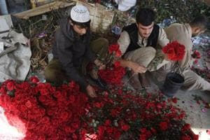 Pakistanis vendors prepare flower bouquets at a roadside stall ahead of Valentine