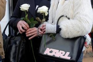 People hold white roses as they stand outside the Chanel fashion boutique after news that German haute-couture designer Karl Lagerfeld, artistic director at Chanel and an icon of the global fashion industry for over half a century, has died, aged 85, in Paris, France, February 19, 2019.