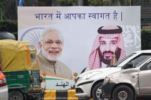 Vehicles drive past a billboard displaying the portrait of Indian Prime Minister Narendra Modi and Saudi Arabian Crown Prince Mohammed bin Salman ahead of his official visit to India, in New Delhi on February 19.