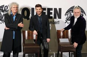 Members of the band Queen, guitarist Brian May (L) and drummer Roger Taylor (R), appear with singer Adam Lambert at a news conference in Berlin December 11, 2014.
