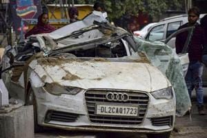 Passers-by look at the mangled remains of an Audi car which collided with a dumper  at Rohini, in New Delhi, Wednesday, Feb. 20, 2019, killing three of the four occupants of the car.