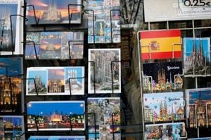 Postcards showing Spanish flag and other tourist attractions are displayed at a souvenirs shop in Spain.