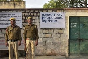 Police officials guard the mortuary where body of prisoner killed in jail is being kept after post mortem, in Jaipu