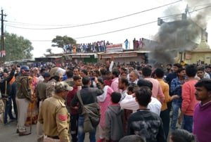 Smoke billows from a property set on fire by protesters in Chitrakoot in Madhya Pradesh after the bodies of two school boys kidnapped on February 12 were found on the banks of the Yamuna river .