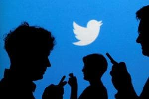 People holding mobile phones are silhouetted against a backdrop projected with the Twitter logo in this illustration picture taken in Warsaw September 27, 2013. REUTERS/Kacper Pempel/Illustration/Files