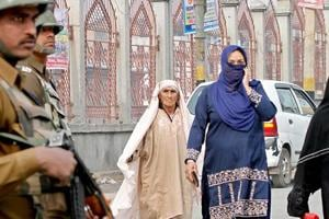 Paramilitary soldiers stand guard as Kashmiri women walk on a street in Srinagar. It is hard to imagine a place in India where a vast majority of people live not having known the simple pleasures of taking a stroll down a road. But this is the reality for most women in Kashmir who have lived for decades in abnormal conditions