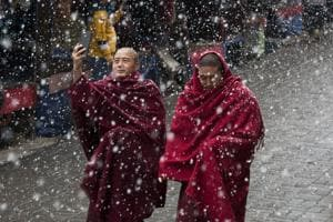 A Tibetan Buddhist monk uses his phone camera as he walks with another in the snow in Dharmsala, February 27, 2019.