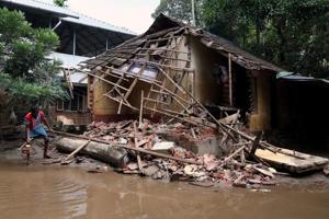 A man removes debris from a collapsed house after floods in Paravur, in the southern state of Kerala on August 23, 2018.