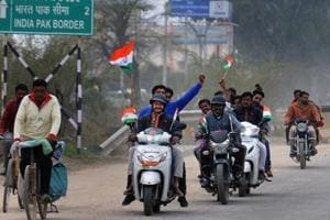People celebrate with tricolour as they wait for the arrival of IAF pilot Wing Commander Abhinandan Varthaman near Attari-Wagah border near Amritsar, Friday.