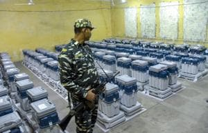 A para-military jawan guards EVMs (Electronic Voting Machines) at a counting centre.