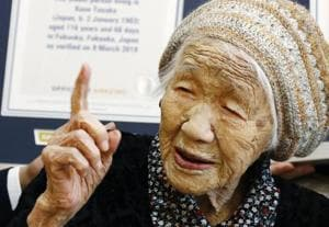 Kane Tanaka, a 116-year-old Japanese woman, gestures after receiving a Guinness World Records certificate, back, at a nursing home where she lives in Fukuoka.