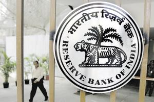 (An Indian pedestrian walks out of The Reserve Bank of India (RBI) building in Mumbai.