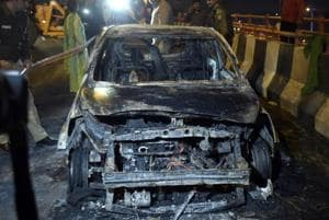 A view of the car that caught fire, resulting the death of three persons, near Akshardham Mandir flyover.