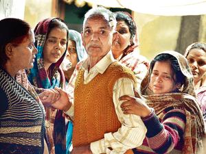 Grieving family members of Sundar Singh at his house in Sihani village in Ghaziabad.