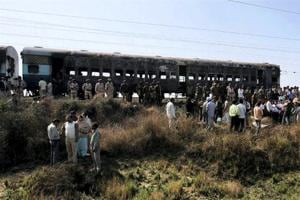 People gather near the bogies of Samjhuata Express after an explosion.