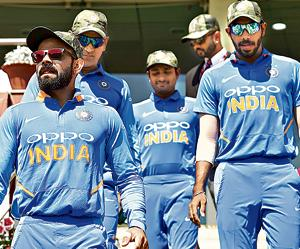 Virat Kohli leads his team out, all wearing camouflage caps, during the series between India and Australia in Ranchi.