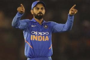 Virat Kohli directs his teammates to their fielding positions.
