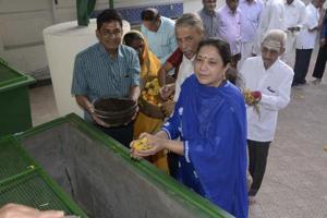 A devotee drops flowers into the composting machine at Bhajan Samaj temple in Ghatkopar.