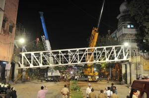 Workers dismantle the bridge near Chhatrapati Shivaji Maharaj Terminus on Friday, a day after its part collapsed.