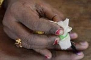 An Indian election official inks a woman's finger after an election.